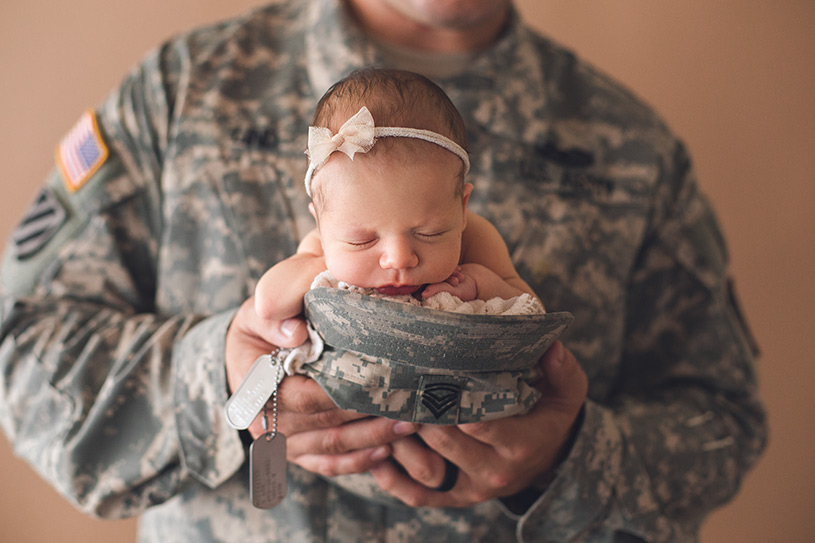 Sweet baby girl held by her military father for her newborn session by nicole monique photography