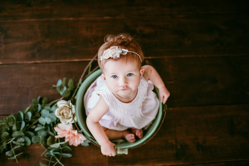 Baby Photography, little girl looking up at the camera out of a bucket