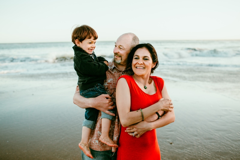 Family Photography, family of three hugging up together at the beach