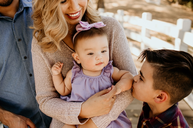 Family Photography, big brother kissing little sister on the arm