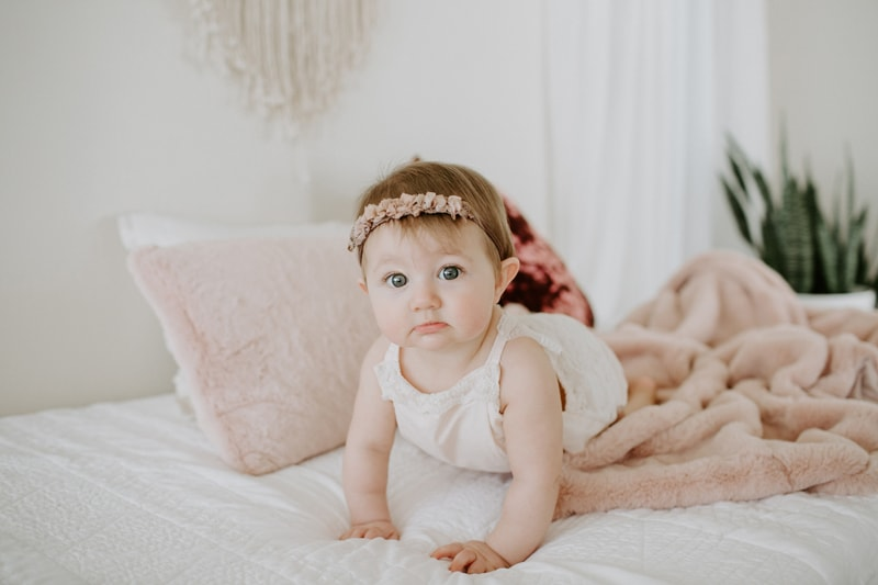 Baby Photography, little girl crawling across a bed