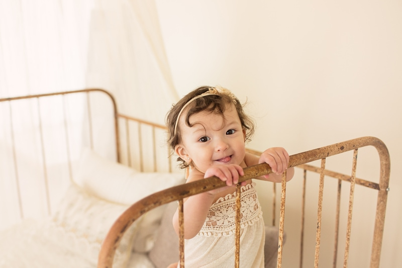 Baby Photography, little girl looking over the edge of a crib