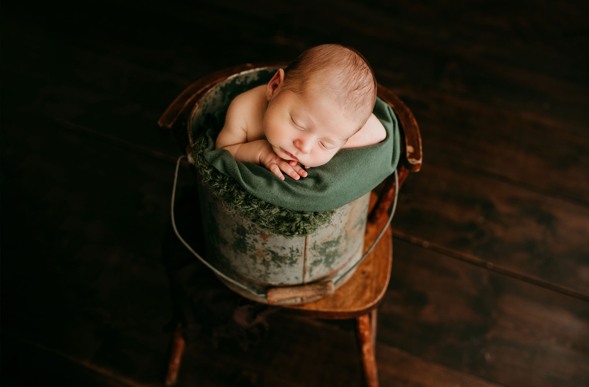Newborn Photography, baby wrapped up in green blanket in bucket