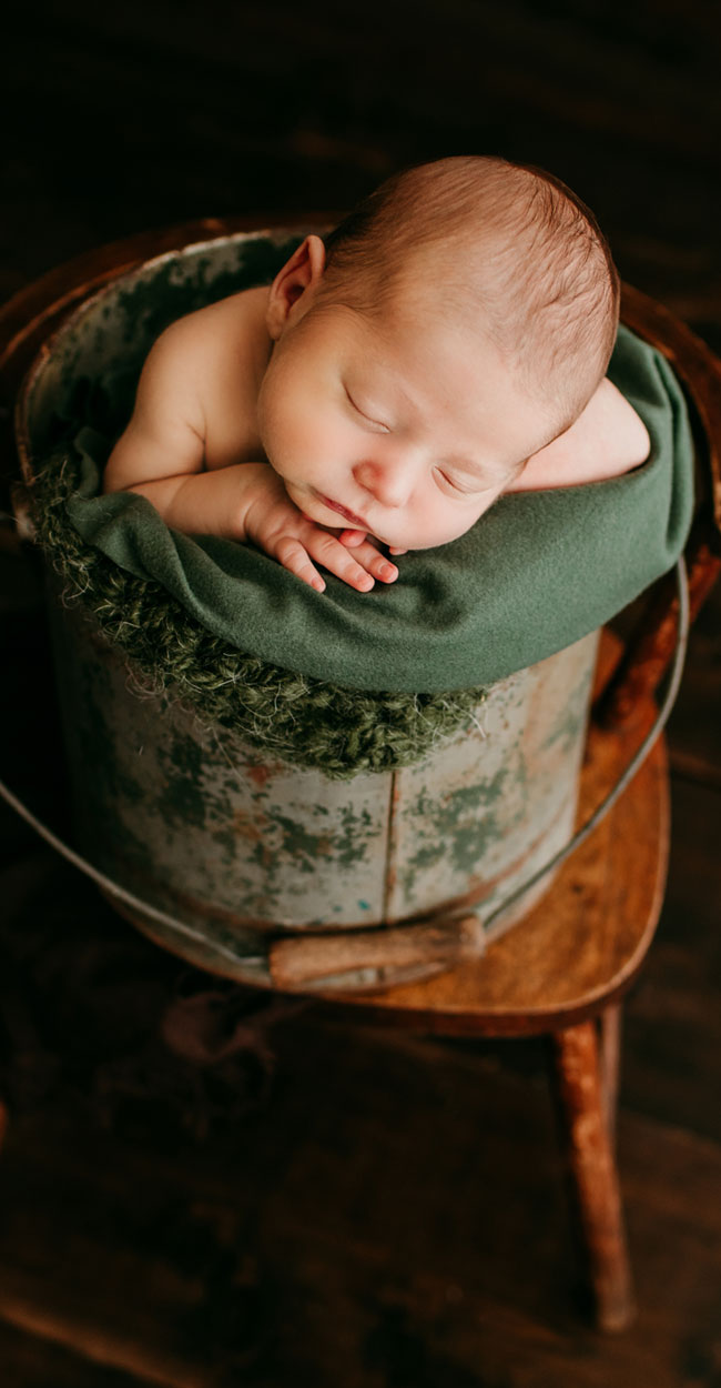 newborn photography, baby wrapped up in a green blanket and sitting in a blanket