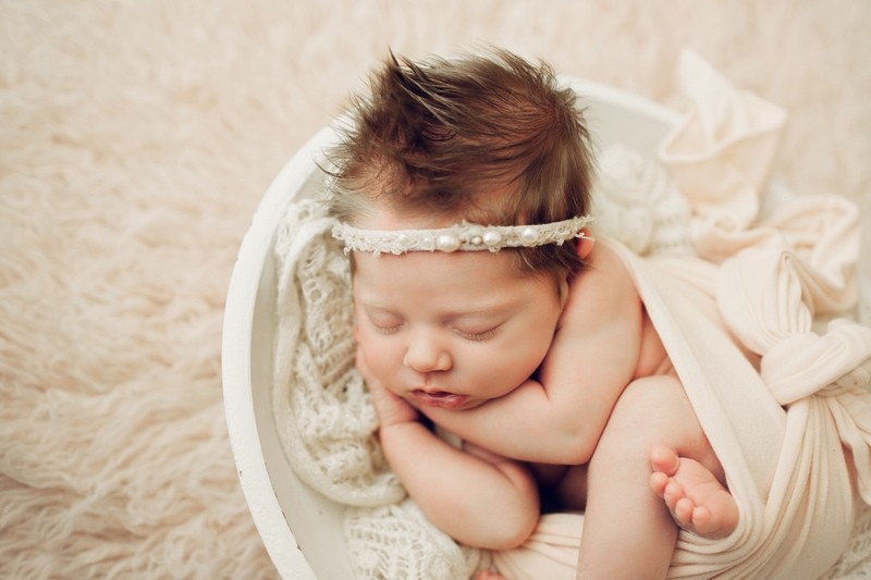 Newborn Photography, baby asleep wrapped up in a white cloth wearing a pearl headband