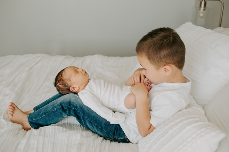 Newborn Photography, baby laying on big brother's legs