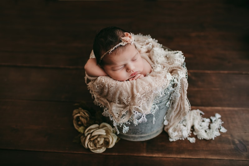 Newborn Photography, baby asleep in a bucket wearing a lace headband