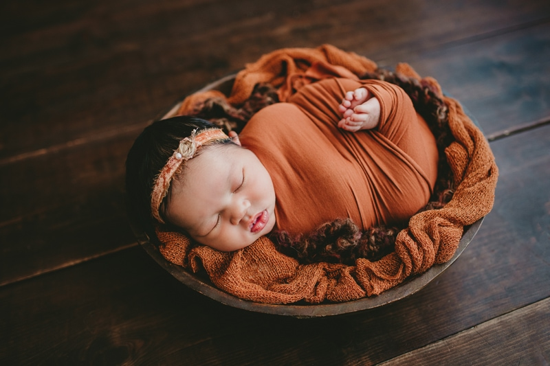 Newborn Photography, baby wrapped up in a burnt orange colored blanket