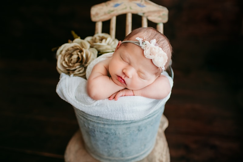 Newborn Photography, baby wrapped up in a white blanket in a bucket