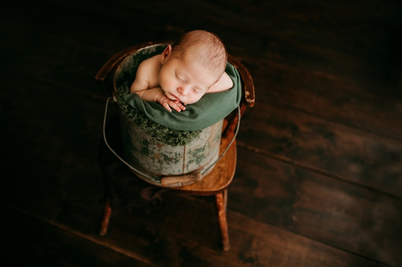 Newborn Photography, baby asleep on a green blanket in a bucket