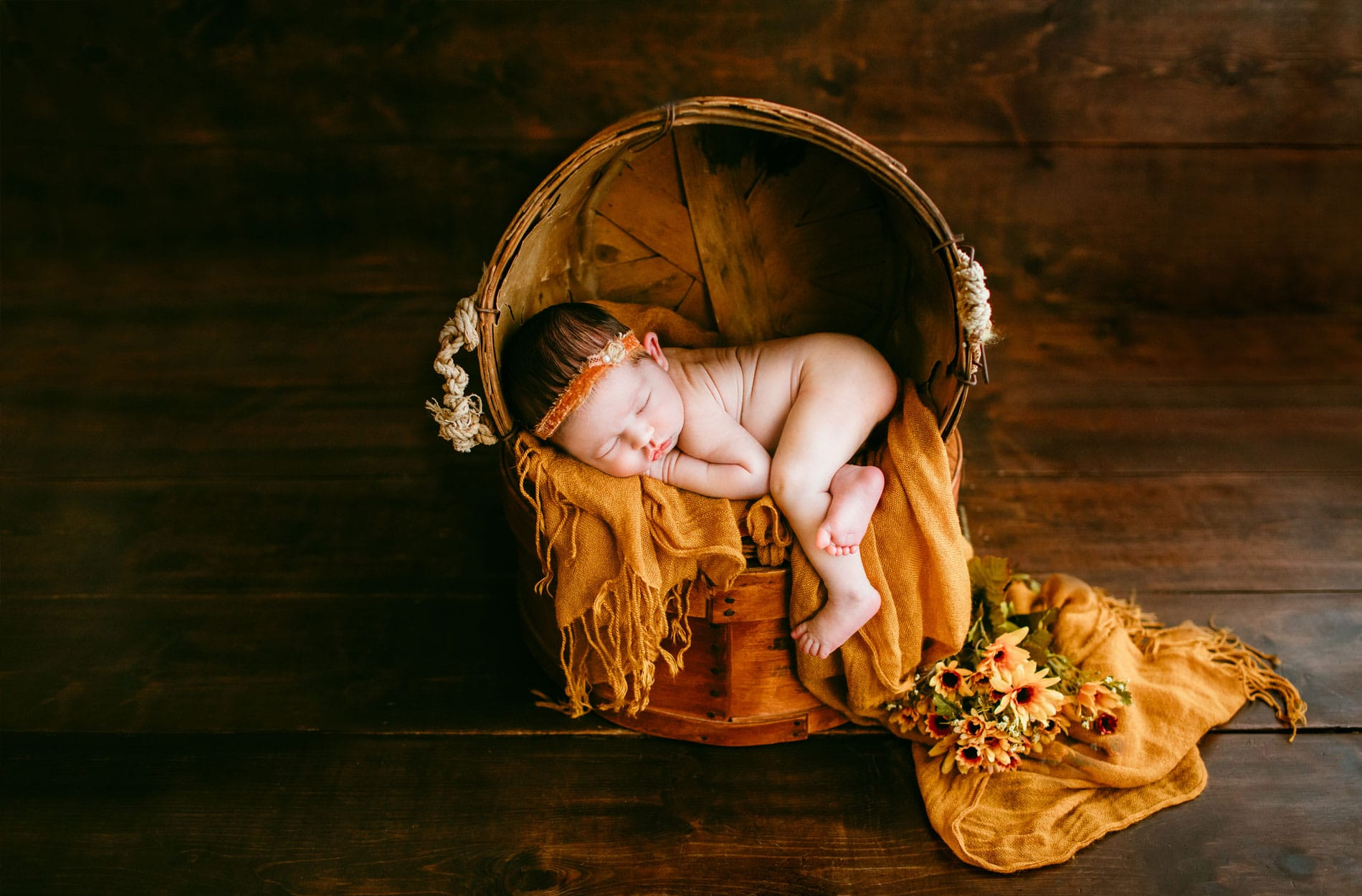 Newborn Photography, baby asleep on a yell blanket in a basket chair