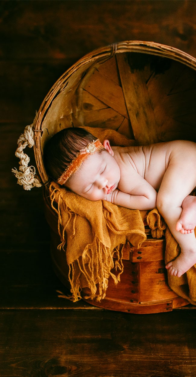 Newborn Photography, close up of sleeping baby in a basket chair